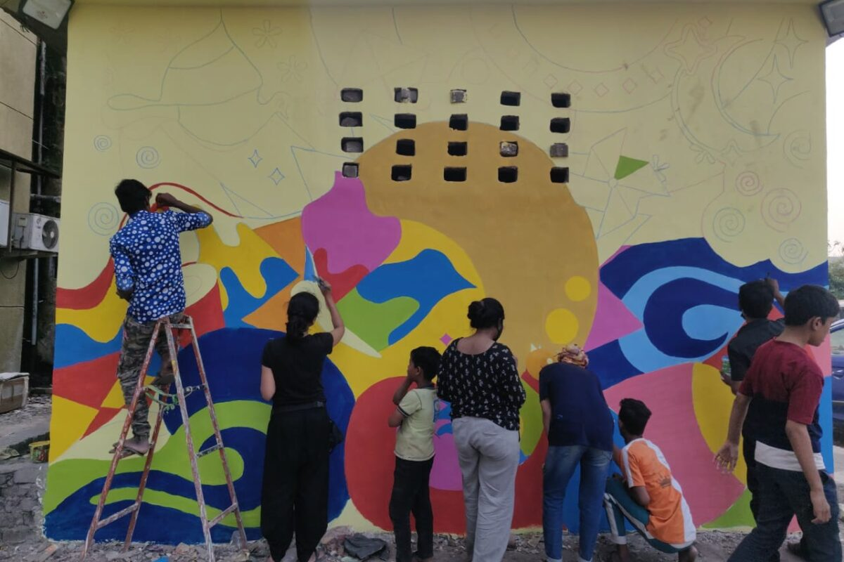 A group of boys and girls painting a wall mural with their backs to the camera