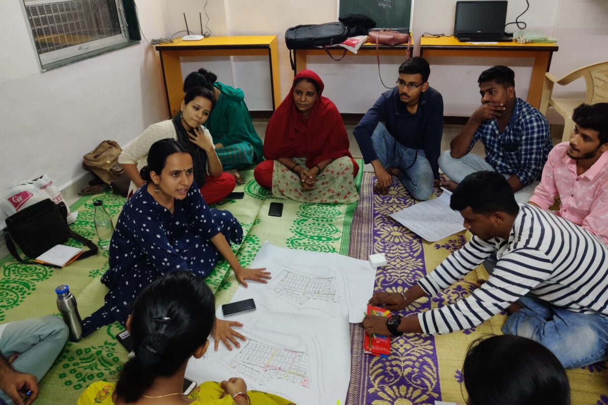 Group of boys and girls sitting around 2 maps and conducting a meeting